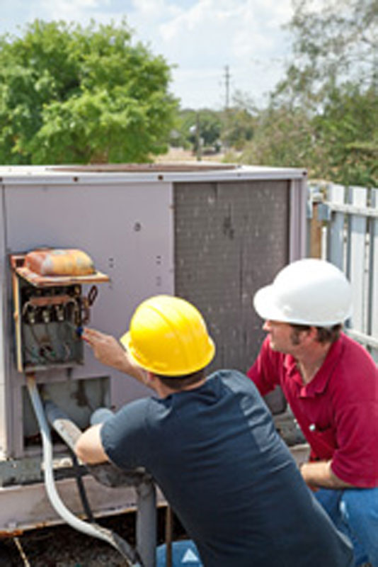 Men in hardhats performing HVAC repair on an air-conditioning unit on a roof